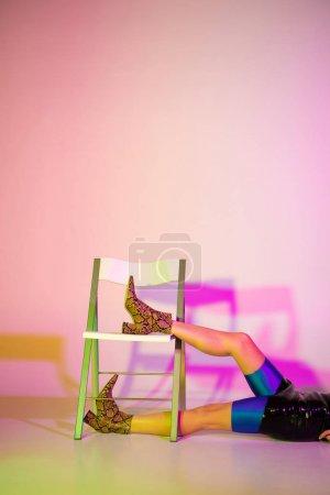 Photo pour Vue recadrée de la femme élégante couchée sur le sol près de la chaise sur violet avec éclairage - image libre de droit
