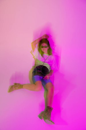 Photo for Motion blur of young woman in sunglasses lying on purple - Royalty Free Image