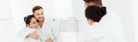 Photo for Panoramic shot of happy man hugging attractive woman while looking at mirror - Royalty Free Image