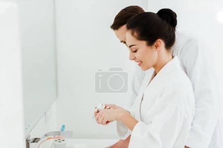 Photo pour Vue recadrée de l'homme restant près du dentifrice de fixation heureux de fille dans la salle de bains - image libre de droit