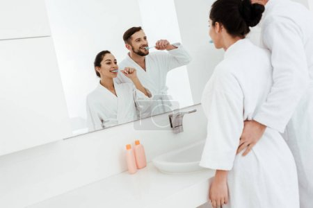 Photo for Cheerful couple looking at mirror and brushing teeth while standing in bathrobes - Royalty Free Image
