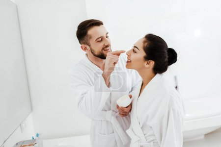 Photo for Cheerful man applying face cream on nose of attractive girlfriend - Royalty Free Image