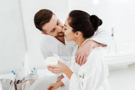 Photo pour Petit ami gai embrassant le récipient heureux de fixation de fille avec la crème de visage - image libre de droit