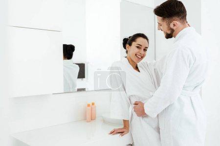 Photo for Handsome bearded boyfriend hugging happy girl in bathrobe - Royalty Free Image