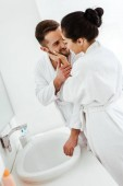 "Постер, картина, фотообои ""brunette girl touching face of handsome man smiling in bathrobe """