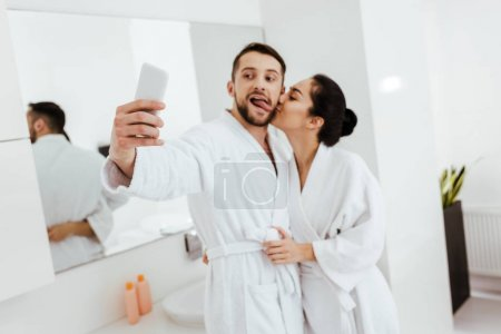 Photo pour Girlfriend kissing cheek of cheerful man showing tongue while taking selfie in bathroom - image libre de droit