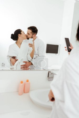 Photo for Selective focus of woman taking photo while kissing with boyfriend in bathroom - Royalty Free Image