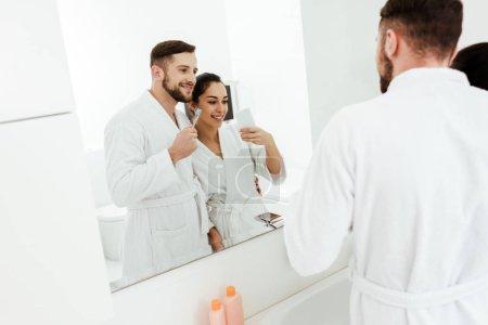 Photo pour Foyer sélectif de la femme gaie prenant la photo avec l'homme heureux retenant la brosse à dents - image libre de droit