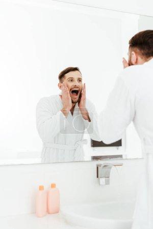 Photo pour Foyer sélectif de l'homme barbu beau regardant le miroir et criant dans la salle de bains - image libre de droit