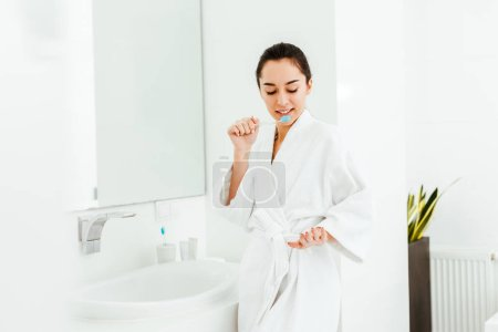 brunette woman holding toothbrush with toothpaste and looking at hand