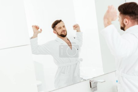 Photo for Selective focus of happy bearded man stretching after wake up in bathroom - Royalty Free Image