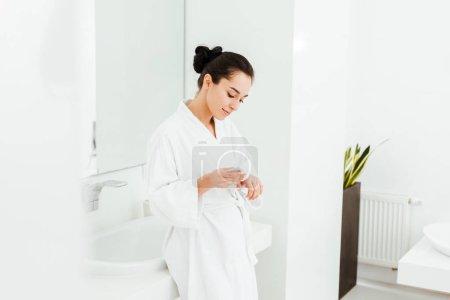 Photo pour Foyer sélectif de la femme attirante appliquant la crème de main dans la salle de bains - image libre de droit