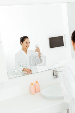 Photo pour Foyer sélectif de jeune femme attirante et heureuse prenant la photo dans la salle de bains - image libre de droit