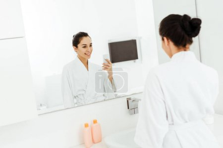 Photo for Selective focus of attractive and cheerful young woman taking photo in bathroom - Royalty Free Image
