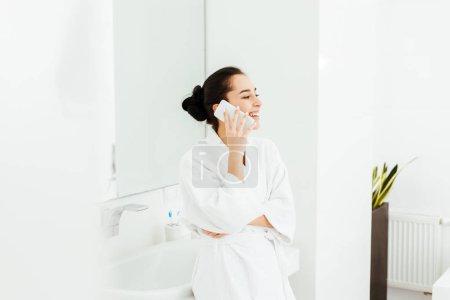 Szczęśliwa młoda kobieta uśmiechnięta podczas rozmowy na smartfonie w łazience