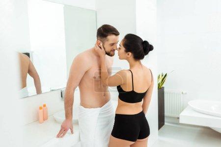 Photo pour Femme attirante dans le visage blanc de contact de sous-vêtements noirs de l'homme torse nu beau - image libre de droit
