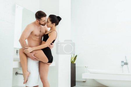 Photo pour Homme barbu passionné tenant jambe de belle fille brune en sous-vêtements noirs - image libre de droit