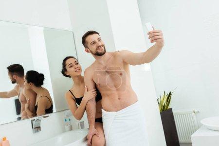 Photo pour Homme torse nu heureux prenant le selfie avec la femme attirante dans la salle de bains - image libre de droit