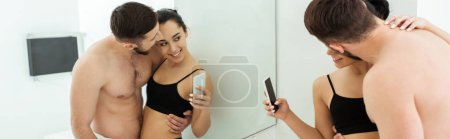 Photo for Panoramic shot of happy young woman taking photo with handsome shirtless man while looking at mirror - Royalty Free Image