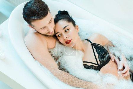 Photo pour Vue au-dessus de l'homme beau se trouvant dans la baignoire avec la femme attirante de brunette dans le soutien-gorge de dentelle - image libre de droit