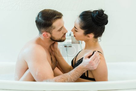 Photo for Bearded shirtless man looking and touching sexy brunette woman in black bra - Royalty Free Image