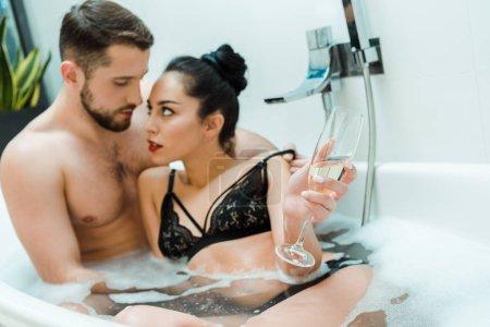 Photo pour Foyer sélectif de femme brune retenant le verre de champagne et regardant l'homme dans la baignoire - image libre de droit