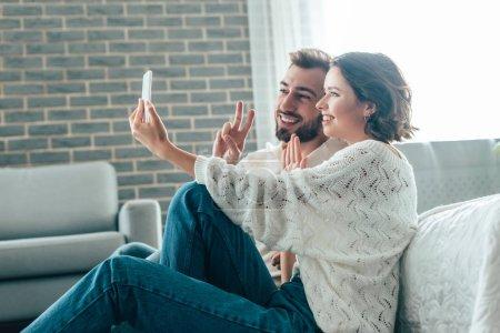 Photo pour Femme heureux agitant la main tout en prenant le selfie avec l'homme affichant le signe de paix à la maison - image libre de droit