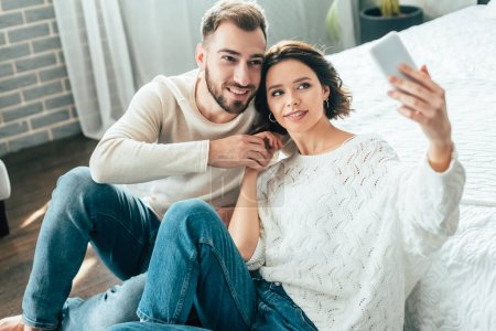 Photo for Selective focus of attractive woman and handsome man holding hands while taking selfie at home - Royalty Free Image