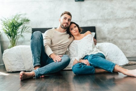 Photo for Handsome man hugging attractive woman while sitting on floor and watching movie at home - Royalty Free Image