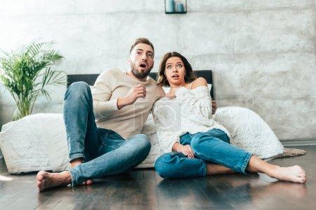Photo pour Homme et femme choqués s'asseyant sur l'étage et regardant le film à la maison - image libre de droit