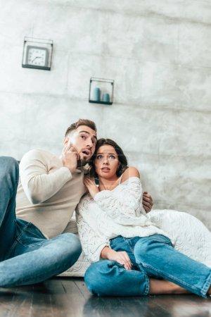 Photo pour Vue d'angle bas du couple choqué s'asseyant sur l'étage et regardant le film à la maison - image libre de droit