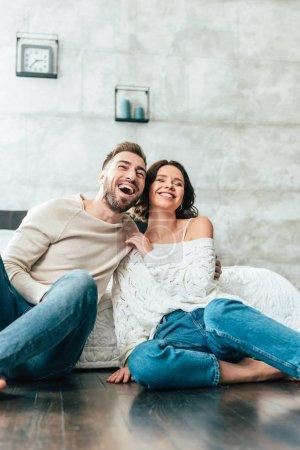 Photo pour Vue bas d'angle de l'homme et de la femme heureux s'asseyant sur l'étage et regardant le film à la maison - image libre de droit
