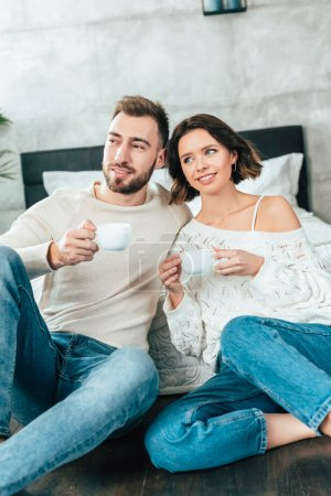 Photo for Happy man and cheerful woman sitting on floor and holding cups with drinks - Royalty Free Image