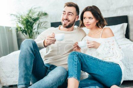 Photo pour Homme heureux et femme attrayante assis et tenant des tasses avec des boissons - image libre de droit