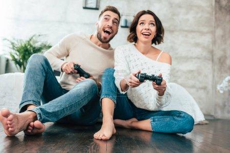 Photo pour Vue bas d'angle de l'homme et de la femme heureux jouant le jeu vidéo à la maison - image libre de droit