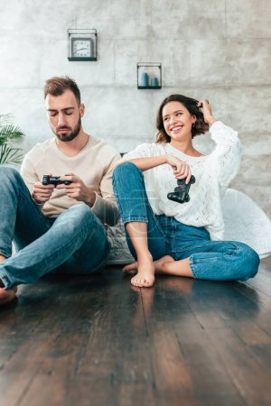 Photo for Low angle view of happy woman looking at upset man holding joystick at home - Royalty Free Image