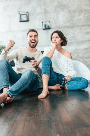Photo for Low angle view of upset woman looking at happy man gesturing while playing video game - Royalty Free Image