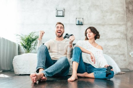 Photo pour Vue à faible angle de la femme attrayante regardant l'homme heureux gestuelle tout en jouant à un jeu vidéo - image libre de droit