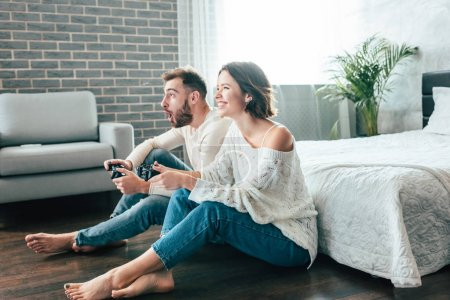 Photo for Happy woman and emotional man playing video game at home - Royalty Free Image