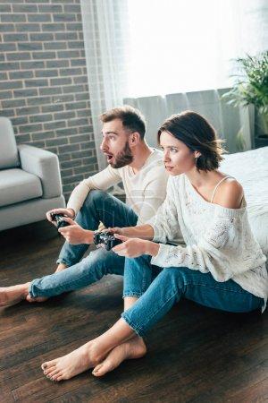 Photo pour Homme choqué et femme attirante jouant au jeu vidéo à la maison - image libre de droit