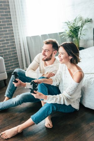 Photo for Happy man and attractive woman playing video game at home - Royalty Free Image