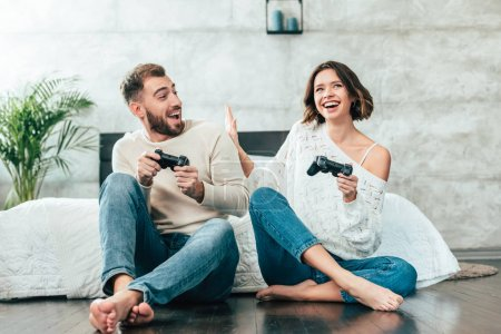 Photo for Surprised man looking at cheerful woman playing video game at home - Royalty Free Image