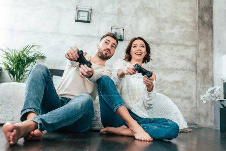 Photo pour Vue bas d'angle de l'homme heureux et de la femme gaie retenant des joysticks à la maison - image libre de droit