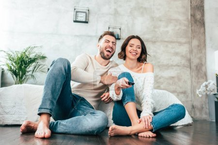 Photo pour Low angle view of happy man sitting on floor near cheerful woman with remote controller - image libre de droit