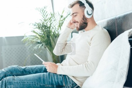 Photo for Happy bearded man using smartphone while listening music in headphones - Royalty Free Image