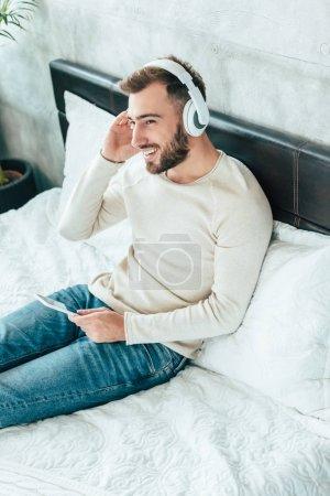 Photo pour Vue aérienne de l'homme barbu heureux en utilisant un smartphone tout en écoutant de la musique dans les écouteurs - image libre de droit