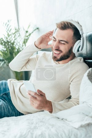 Photo for Happy bearded man holding smartphone while listening music in headphones - Royalty Free Image