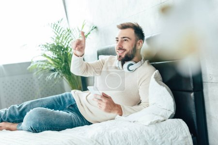 selective focus of happy bearded man in headphones holding smartphone and pointing with finger in bedroom