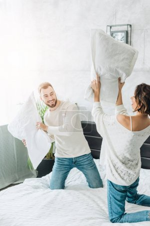 Photo for Happy bearded man having pillow fight with cheerful woman on bed - Royalty Free Image