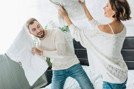 Photo for Selective focus of happy bearded man having pillow fight with cheerful woman on bed - Royalty Free Image